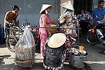 Two women chat on a sidewalk in District 4, Ho Chi Minh City, Vietnam. Sept. 9, 2011.