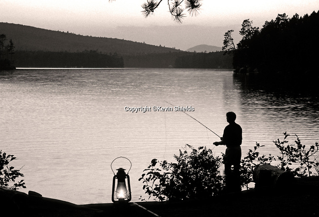 Fishing on Upper Togue Pond at twilight with lantern, Baxter State Park, Maine, USA, Piscataquis County