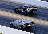 Sept. 15, 2012; Concord, NC, USA: NHRA pro mod driver Leah Pruett (far lane) races alongside Roger Burgess during qualifying for the O'Reilly Auto Parts Nationals at zMax Dragway. Mandatory Credit: Mark J. Rebilas-
