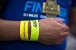 """© Joel Goodman - 07973 332324. 15/10/2017 . Manchester , UK . Athlete with a """" We Stand Together """" wristband reaches the finish line in the Greater Manchester Half Marathon in Old Trafford . Photo credit : Joel Goodman"""