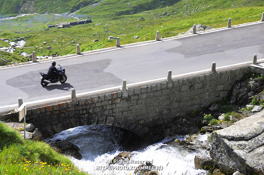 Biker on bridge over Alpine spring