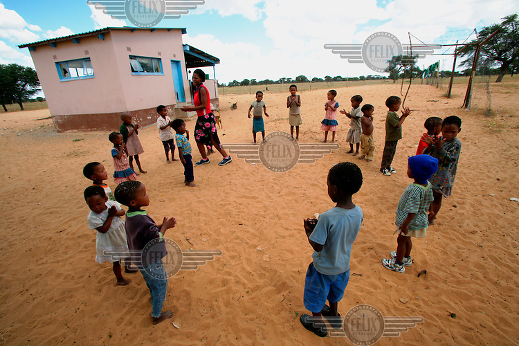 A teacher playing a game with the children outside a community school for San children in a poor neighbourhood.