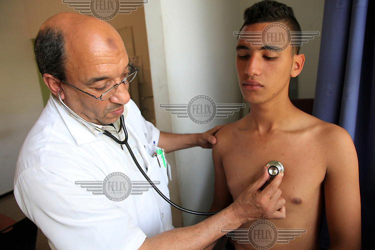 A medic examines a young man at the 'youth friendly' Youssoufia Centre.
