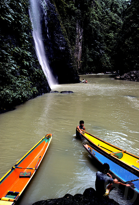 PANGASINAN WATERFALL, PANGASINAN WATERFALL in the Philippines with a traditional boat and boatman in the forground