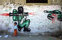 """A mural showing a Palestinian fighter shooting an RPG rocket to an Israeli tank is seen in the """"Beach refugee camp"""", in Gaza strip, June 9, 2004. Photo by Quique Kierszenbaum"""