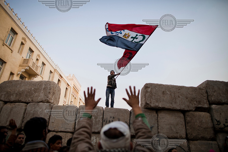 A man, standing on a barricade erected by the Egyptian military to prevent protesters accessing the cabinet building, waves a flag. The demonstrators were calling for an immediate transfer of power from Egypt's military rulers, SCAF (Supreme Council of the Armed Forces), to a civilian government