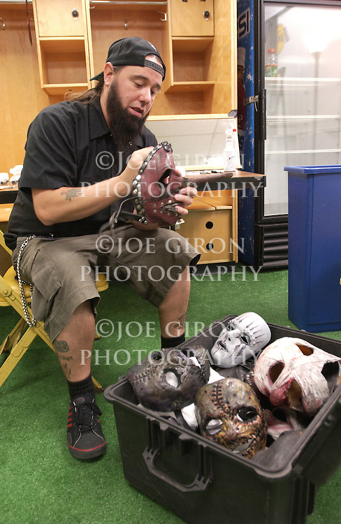 """Slipknot band assistant, """"Tongs"""" wipes the  band's masks prior to their performance."""