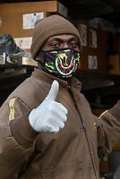 New York, New York City. New Yorkers are told to stay home during the corona virus, (COVID-19) so New York has become eerily empty. UPS delivery man wearing a face mask he got when he was with his son at Disneyland.