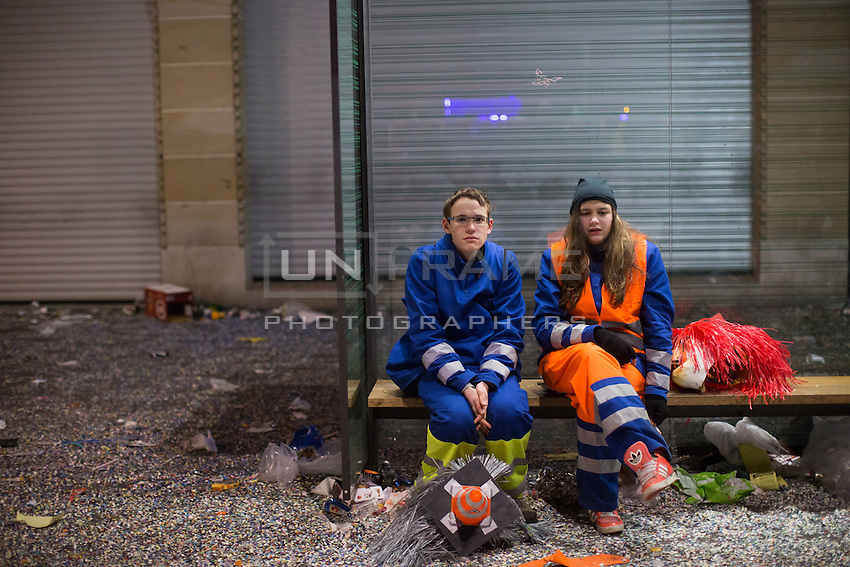 Participants in Fasnacht, the Carnival of Basel, sit at a tram stop surrounded by remnants of the festivities, as the celebrations wind down on the final day. Basel, Switzerland. Feb. 26, 2015.