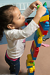 Education Preschool 3-4 year olds girl building with colored plastic stacking blocks