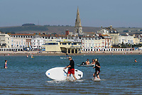 BNPS.co.uk (01202 558833)<br /> Pic: Graham Hunt/BNPS<br /> Date: 7th September 2021.<br /> <br /> Sunbathers flock to the beach to enjoy the scorching hot sunshine at the seaside resort of Weymouth in Dorset.<br /> <br /> Paddle boarders in the calm sea with their board.
