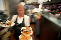 Waitress with arms filled with orders.