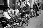 1970s poverty UK. Mixed race family mother and child out shopping buying second hand old clothes Battersea south London   1979 England