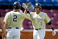 Carlos Lopez #3 of the Wake Forest Demon Deacons high fives teammate Mark Rhine #2 after hitting a solo home run against the Florida State Seminoles at Wake Forest Baseball Park on March 25, 2012 in Winston-Salem, North Carolina.  The Demon Deacons defeated the Seminoles 7-5.  (Brian Westerholt/Four Seam Images)