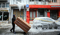 Pictured: A man delivering a fridge freezer walks past cars covered in thick ice in central Salonika, Greece. Monday 09 January 2017<br /> Re: Severe cold weather affects Salonica in northern Greece