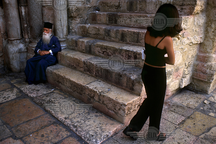 Priest and tourist at the entrance to the tomb of Jesus Christ in the Church of the Holy Sepulchre.