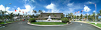 "Panorama of the popular tourist attraction, Polynesian Cultural Center on Oahu's north shore, featuring the """"thatched roof"""" entrance surrounded by palm trees. Bright blue sky with wispy clouds in background."