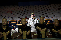 "Ray Roderick, Writer & Director, poses for pictures inside the Red Theatre while martial artists / dancers warm up in the foreground. ""Chun Yi: The Legend of Kungfu"" is an entertaining piece of drama, which has been showing for consecutive five years in Beijing, China."
