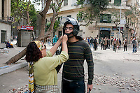 A woman helping an anti government protester put on a helmet. Throughout Friday, 4 February, anti government protesters protected their positions from pro Mubarak supporters around Tahrir square, the scene of heavy clashes between pro and anti government protesters. Continued anti-government protests take place in Cairo calling for President Mubarak to stand down. After dissolving the government and allowing for talks with opposition parties Mubarak still refuses to step down from power...