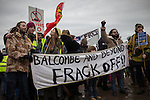 "© Joel Goodman - 07973 332324 . 26/01/2014 . Salford , UK . A banner that reads "" Balcombe and beyond frack off "" . Approximately 500 protesters march to an iGas fracking exploration site at Barton Moss , Salford , today (Sunday 26th January 2014) . They walk along the A57 road , blocking traffic as they do . A long term protest camp has been established on an access road leading to the site and today (26th January) protesters from other areas of the country travelled to the site to join with other protesters against fracking . Photo credit : Joel Goodman"