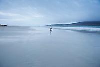 Woman walks along Luskentyre beach on overcast day, Isle of Harris, Western Isles, Scotland