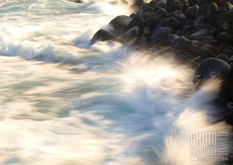 Ocean waves splash against the rocky shoreline of Honokohau Beach near Honokohau Harbor, Kailua-Kona, Big Island.