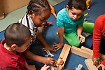 Education Preschool 3-4 year olds group of children playing with toy animals and wood blocks