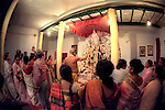 INDIA (West Bengal - Calcutta)  2006,A ritual of evening worship called 'ARATI' at Mullick family house(one of the well known families in South Calcutta) on one of the days of Durga Puja Festival. Durga Puja Festival is the biggest festival among bengalies.  As Calcutta is the capital of West Bengal and cultural hub of  the bengali community Durga puja is held with the maximum pomp and vigour. Ritualistic worship, food, drink, new clothes, visiting friends and relatives places and merryment is a part of it. In this festival the hindus worship a ten handed godess riding on a lion armed wth all possible deadly ancient weapons along with her 4 children (Ganesha - God for sucess, Saraswati - Goddess for arts and education, Laxmi - Goddess of wealth and prosperity, Kartikeya - The god of manly hood and beauty). Durga is symbolised as the women power in Indian Mythology.  In Calcutta people from all the religions enjoy these four days of festival in the moth of October. Now the religious festival has become the biggest cultural extravagenza of Calcutta the cultural capital of India. Artistry and craftsmanship can be seen in different sizes and shapes in form of the idol, the interior decor and as well as the pandals erected on the streets, roads and  parks.- Arindam Mukherjee