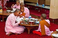 Myanmar, Burma.  Zayar Thein Gyi Nunnery, near Mandalay.  Buddhist Nuns Having Lunch, Sitting on the Floor.  Buddhist Monks and Nuns shave their heads while in service.
