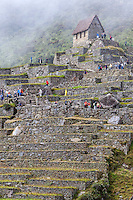 Peru, Machu Picchu.  Guardhouse and Terraces, with Newly Arriving Tourists.