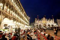Turisti seduti di sera nei caffe' all'aperto in Piazza San Marco, a Venezia. Sullo sfondo, la Basilica.<br /> Tourists sit at outdoor cafes in St. Mark's Square, Venice, in evening light. In background, St. Mark Basilica.<br /> UPDATE IMAGES PRESS/Riccardo De Luca