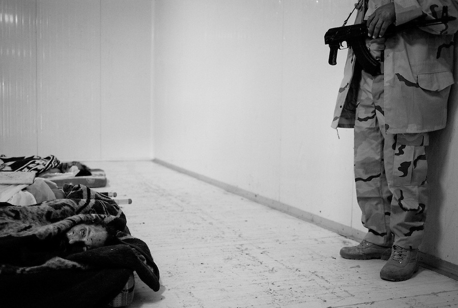 An NTC soldier guards the bodies of Muammar Gaddafi, Mutassim Gaddafi and Abu Bakr Younis inside a walk in freezer at the African Tunisian Souq in Misrata, Libya, Saturday October 22, 2011. The confirmed death of Moammar Gaddafi brings closure to the Libyan population after an 8 month uprising turned revolutionary war.