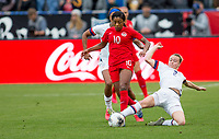 Emily Sonnett #2 of the United States slide tackles Ashley Lawerance #10 of Canada