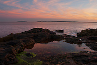 Sunset along the coast of Acadia National Park in  Maine with a tidal pool in the foreground