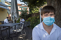 Switzerland. Canton Ticino. Locarno. Restaurant Vallemaggia. At the end of the lunch service. Guglielmo Hug and his colleagues, all waiters, wear a mask on their faces to protect themselves and customers from the Coronavirus (also called Covid-19). Guglielmo Hug is a dancing member of MOPS_DanceSyndrome which is an independent Swiss artistic, cultural and social organisation operating in the field of contemporary dance and disability. It is composed only of Down dancers. Down syndrome (DS or DNS), also known as trisomy 21, is a genetic disorder caused by the presence of all or part of a third copy of chromosome 21 It is usually associated with physical growth delays, mild to moderate intellectual disability, and characteristic facial features. 29.09.2020 © 2020 Didier Ruef