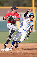 Scott Kingery (25) of the Arizona Wildcats tries to avoid Kevin Kramer (7) of the UCLA Bruins while throwing to first base during a game at Jackie Robinson Stadium on May 16, 2015 in Los Angeles, California. UCLA defeated Arizona, 6-0. (Larry Goren/Four Seam Images)