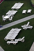 Deck chairs are cleaned and lined in near-perfect lines before sunrise in anticipation of sunbathers in Virginia Beach, Va..