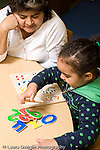 Educaton preschool  3-4 year olds female teacher sitting with girl at table as she plays with wooden puzzle made of numbers