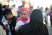 Arequipa, Peru. Young girl (toddler, Peruvian) looks around as her mother carries her on city street. No MR. ID: AL-peru.