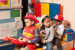 Education Preschool 3-4 year olds group of three children pretend play driving in emergency vehicle or fire truck