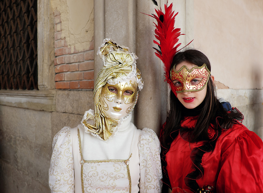 Women dressed in traditional mask and costume for Venice Carnival standing at Doge's Palace, Piazza San Marco, Venice, Veneto, Italy