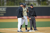 Wake Forest Demon Deacons head coach Tom Walter (16) talks to Patrick Frick (5) as third base umpire Barry Chambers looks on during the game against the Notre Dame Fighting Irish at David F. Couch Ballpark on March 10, 2019 in  Winston-Salem, North Carolina. The Demon Deacons defeated the Fighting Irish 7-4 in game one of a double-header.  (Brian Westerholt/Four Seam Images)