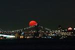The moon rises behind the Brooklyn bridge in New York City