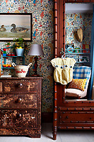 The child's bedroom is furnished with a distressed wooden chest of drawers and a mirrored wardrobe against a cheerful 'Alice in Wonderland' wallpaper