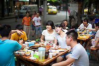 """A group of friends who live in the neighborhood eat at He Wang Shi Chuan Chuan Xiang Huo Guo, a skewer-style hotpot restaurant popular with locals on Tiyu Road in Chongqing, China. The girl in white, who asked not to be named, said that it's one of their favorite places the hotpot flavor is so good.  """"We like the atmosphere. It's a typical Chongqing place: friends sit together and it's hot out and you all sweat together."""" She works in real estate and thinks that places like this won't survive as neighborhoods develop.<br /> <br /> Individual servings of meat, vegetables, and tofu, are placed on skewers which diners choose to add to their table's hotpot. The restaurant, which has many favorable online reviews, often has a long wait for tables."""