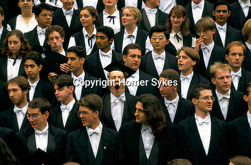 Oxford, Oxfordshire. 1995<br /> With his mortarboard cockeyed, bow tie askew, fatigued and yawning a Magdalen College student takes centre stage for the annual group matriculant's photograph.