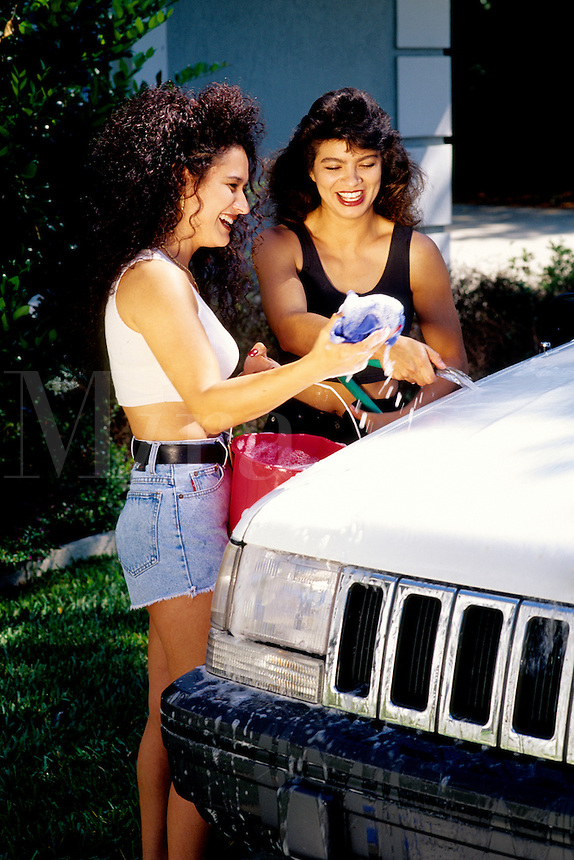 Lesbian couple having fun while washing their sport-utility vehicle car.