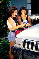 Lesbian couple having fun while washing their sport-utility vehicle car.