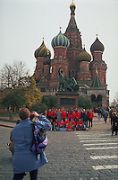 Tourists pose in front of and take pictures of St. Basil's Cathedral in Red Square. Moscow, Russia.
