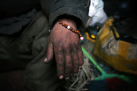 MONGOLIA. Ulaan Baatar. A delicate bracelet hangs from the wrist of the grandfather Battur,55. He is among 50% of Mongolians whose religion is Buddhist Lamaist.As the global financial crisis grips Asia, Mongolia is feeling the implications first hand as the country suffers from rising inflation pushing the price of food and fuel ever upwards. For the country's homeless, who live in sewers and abandoned garages in the capital and already face extreme discrimination and are denied access to basic health and social care, their lives are hanging in the balance. 2008